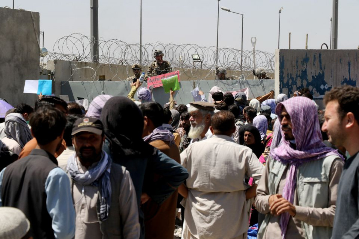 Crowds of people show their documents to U.S. troops outside the airport in Kabul, Afghanistan August 26, 2021.