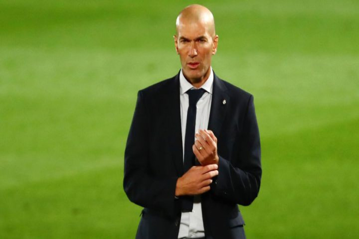 Zinedine Zidane, former coach of Real Madrid, faces a journalist in the street