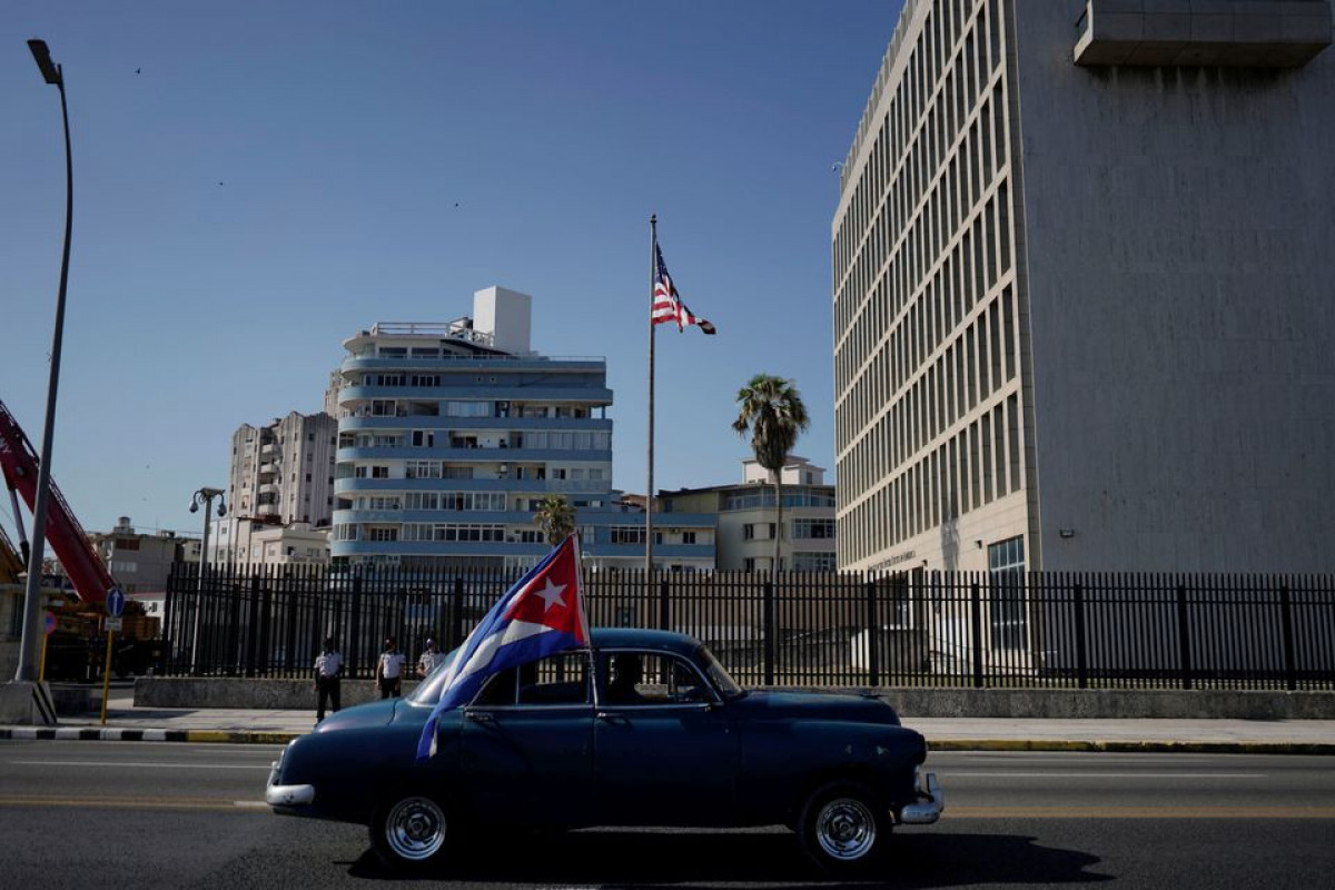 A vintage car passes by the U.S. Embassy carrying a Cuban flag during a motorcade in protest against the trade embargo on Cuba by the U.S. in Havana, Cuba, March 28, 2021.